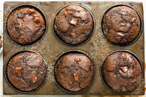 Overhead, close-up photo of double chocolate muffins in a muffin baking pan.