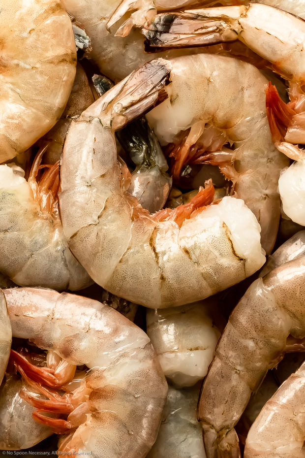 Overhead, close-up photo of raw, large shell-on shrimp- one of the main ingredients in homemade bisque recipe.
