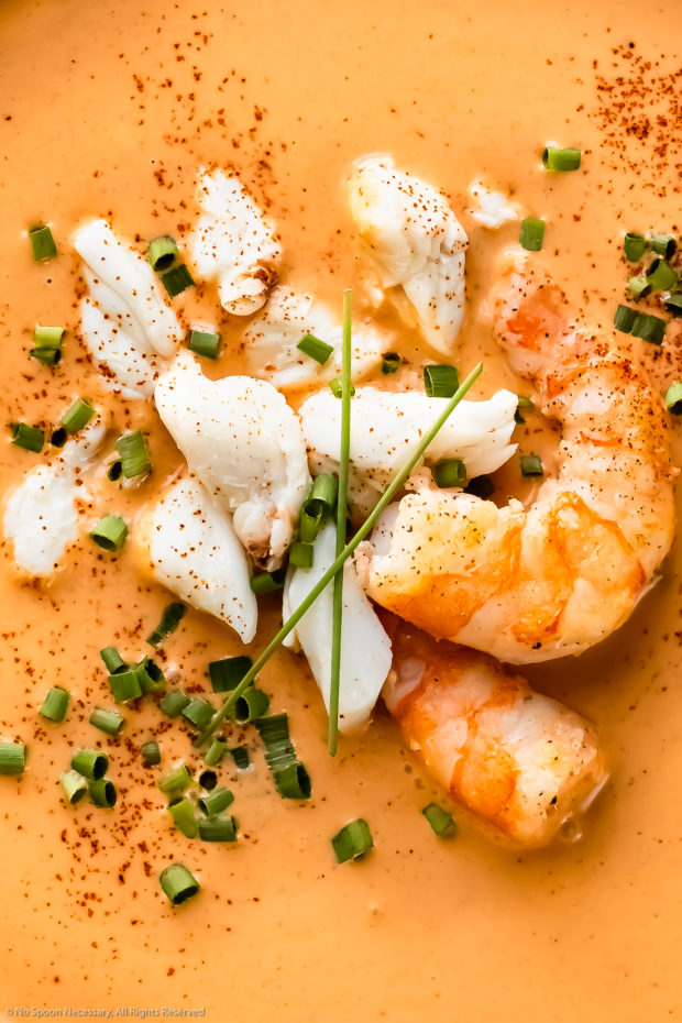 Overhead, close-up photo of Seafood bisque topped with lump crab and shrimp.