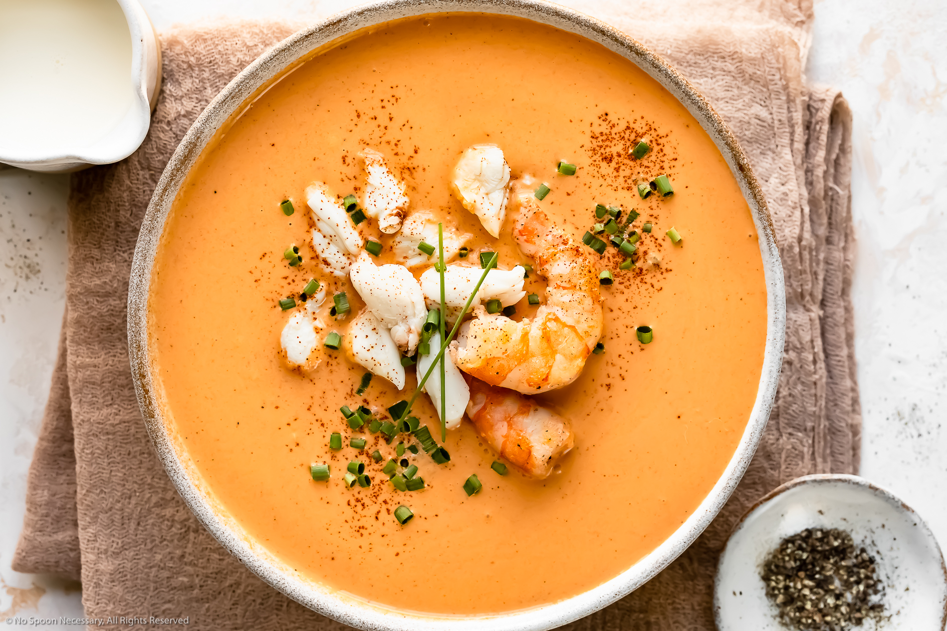 Overhead photo of Shrimp & Crab Seafood Bisque garnished with snipped chives in a white soup bowl with a ramekin of fresh cracked pepper and a small pitcher of cream next to the bowl.