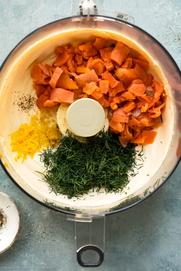 Overhead photo of a food processor bowl filled with whipped cream cheese, smoked salmon, lemon zest, fresh dill and cracked black pepper - photo of step 2 of the recipe.