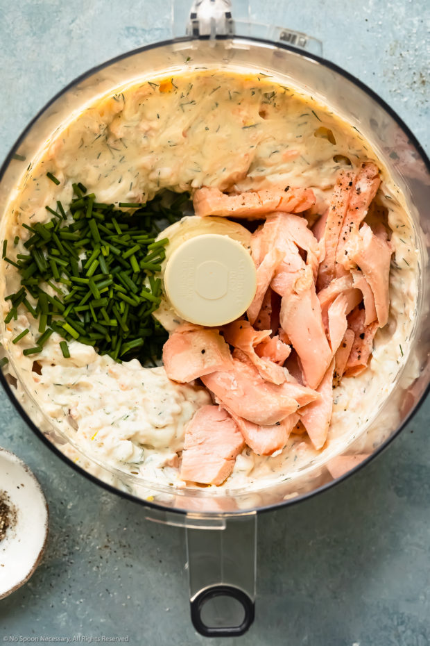 Overhead photo of a food processor bowl filled with smoked salmon whipped cream cheese and topped with flaked wild salmon and chives - photo of step 3 of the recipe.