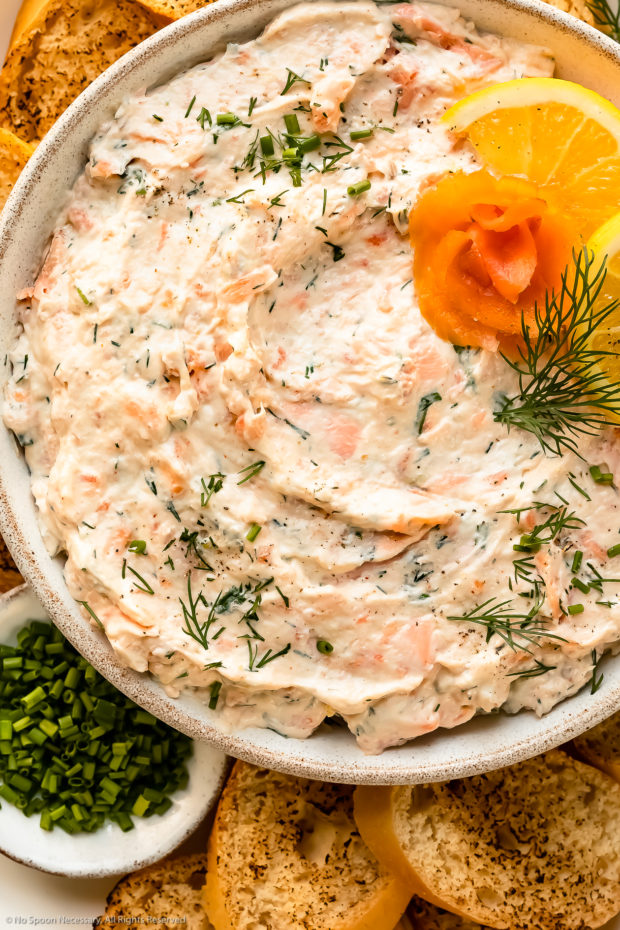 Overhead photo of smoked salmon spread topped with fresh dill in a white serving bowl with a ramekin of snipped chives and crusty slices of bread next to the bowl.
