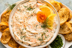 Overhead photo of smoked salmon dip garnished with lemon slices and fresh dill in a white serving bowl with toasted slices of baguette surrounding the bowl.