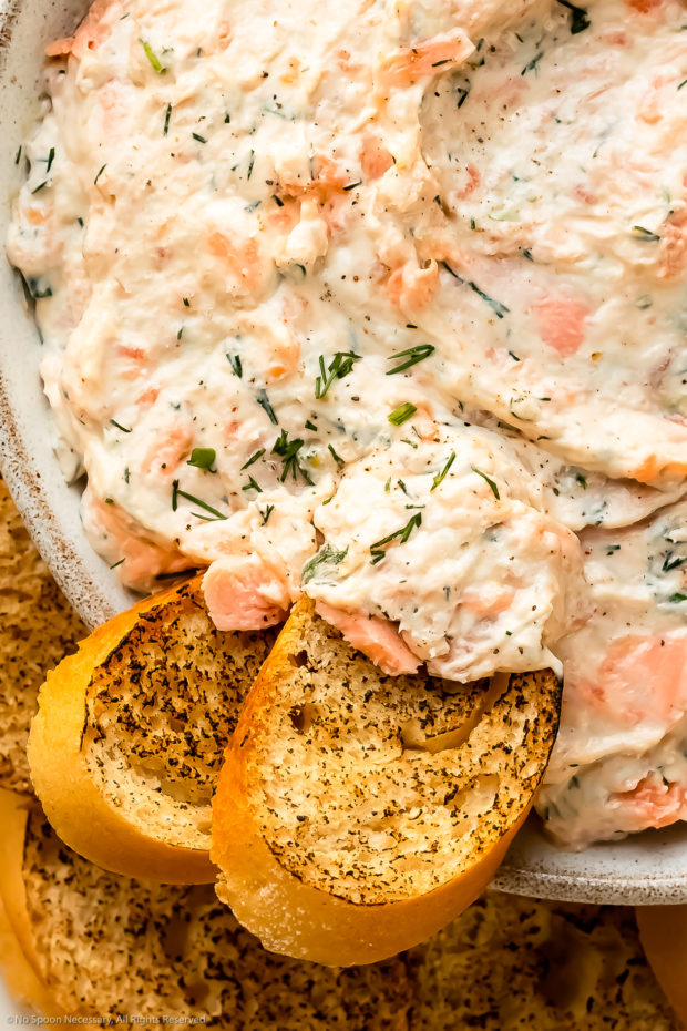 Overhead, close-up photo of two slices of toasted baguette dipped into salmon spread.