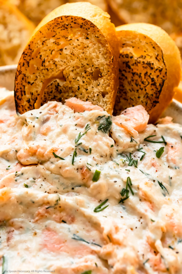 Angled, close-up photo of two slices of crostini dipped into smoked fish dip.
