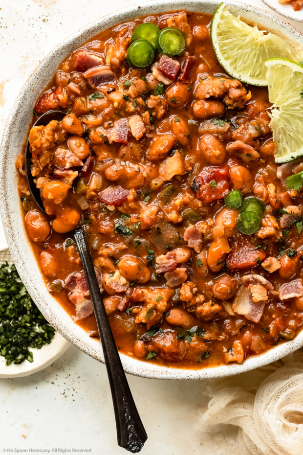 Overhead photo of Tex-Mex pinto beans with bacon and chorizo in a white serving bowl with a serving spoon inserted into the beans.