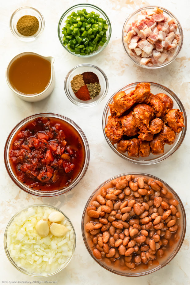 Overhead photo of all the ingredients needed to make Mexican Pinto Beans neatly organized in individual glass bowls on a white wood surface.