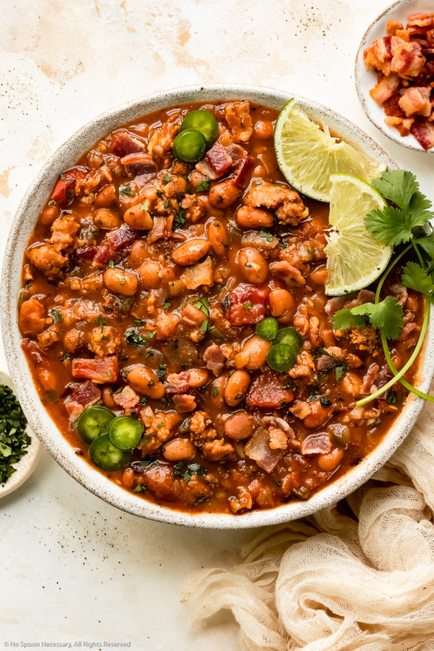 Overhead photo of Mexican Charro Pinto Beans garnished with lime wedges and fresh cilantro in a white serving bowl with ramekins of crumbled bacon and chopped cilantro next to the bowl.
