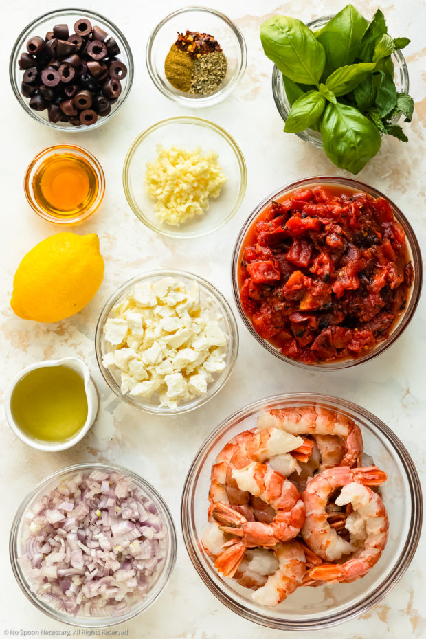 Overhead photo of all the ingredients needed to make Shrimp Saganaki neatly organized in individual glass bowls.