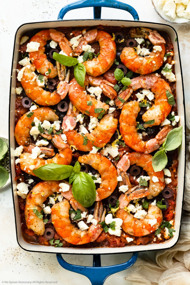 Overhead photo of baked Greek shrimp with tomatoes, olives and feta in a blue baking dish with ramekins of crumbled feta and fresh basil next to the pan.