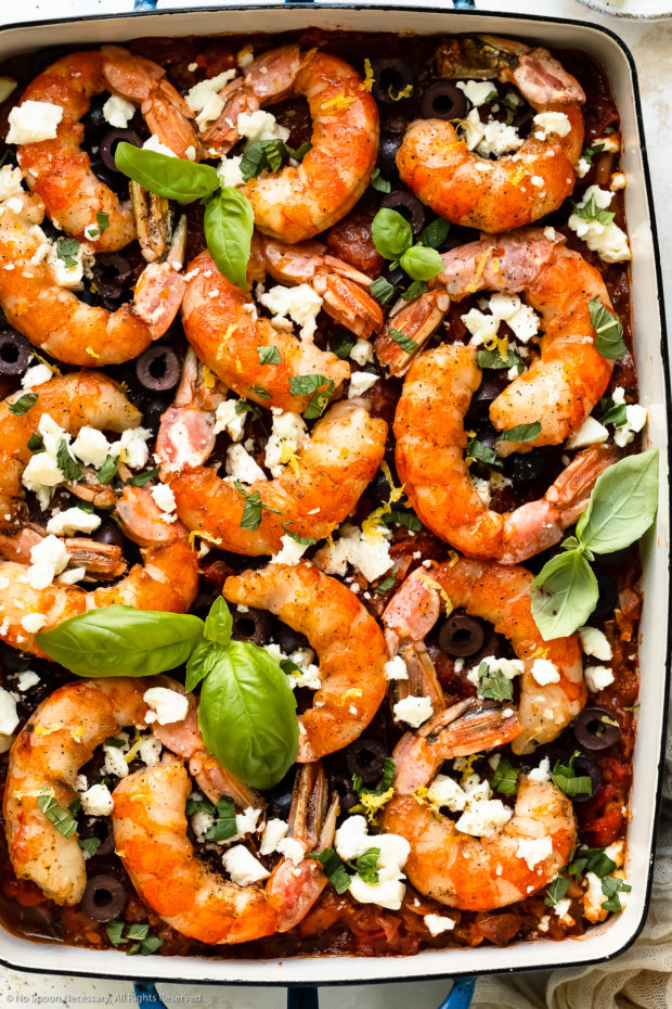 Overhead photo of baked shrimp saganaki with tomatoes and feta in a 9x13-inch baking dish.