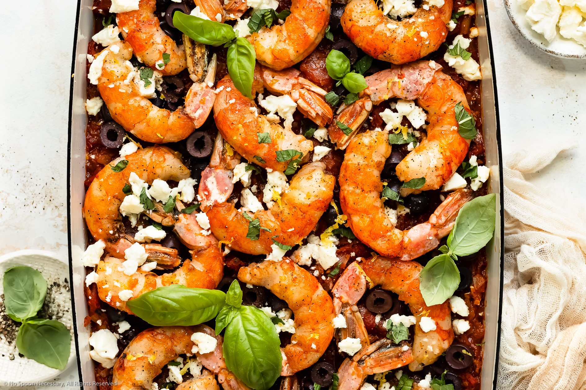 Overhead, landscape photo of baked Greek shrimp with tomatoes, olives and feta in a blue baking dish with ramekins of crumbled feta and fresh basil next to the pan.
