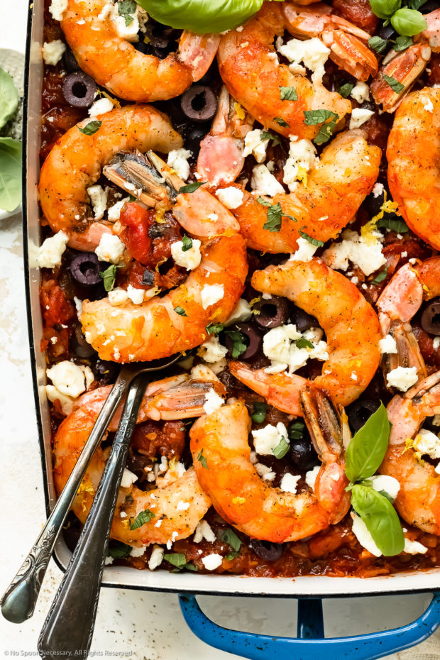 Overhead, close-up photo of Greek shrimp saganaki in a large blue baking dish with two serving spoons lifting up an individual shrimp with tomatoes.