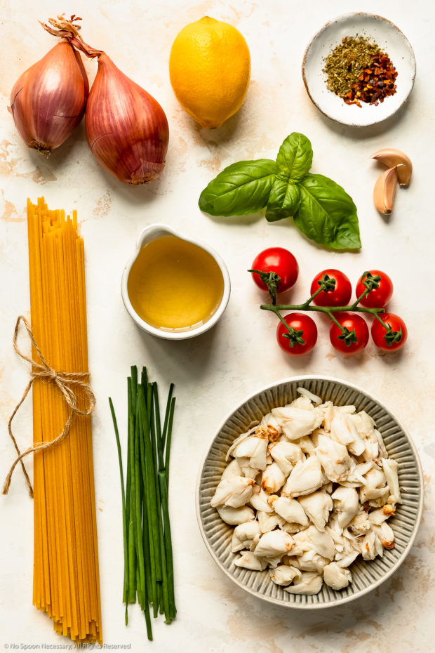 Overhead photo of all the ingredients needed to make crab linguine recipe neatly organized by individual ingredient on a white wood surface.