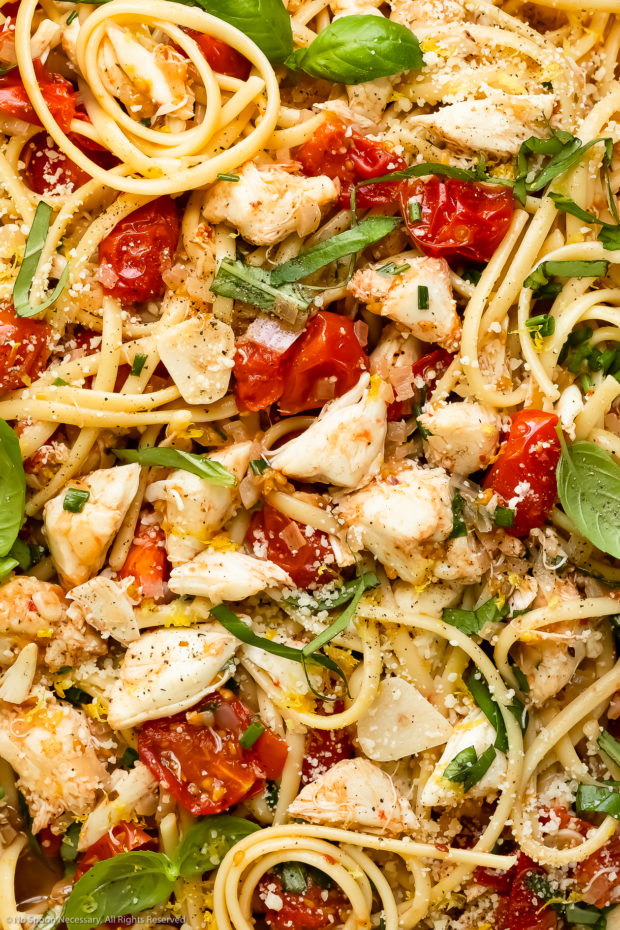 Overhead close-up photo of crab meat pasta garnished with parmesan and fresh basil.