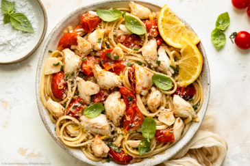 Overhead photo of a white bowl containing crab linguine in wine sauce garnished with fresh basil and lemon wedges.