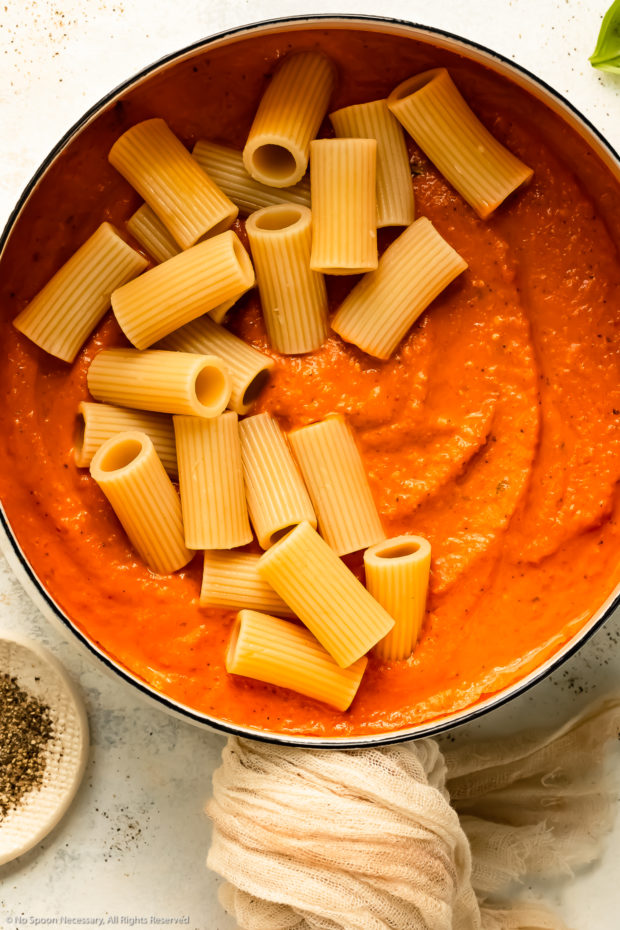 Overhead photo of red pepper sauce topped with rigatoni noodles in a large white saucepan.