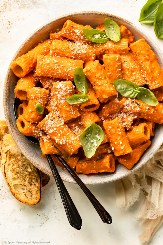 Overhead photo of Roasted Red Pepper Pasta topped with grated parmesan and fresh basil in a white bowl with two serving spoons inserted into the pasta.