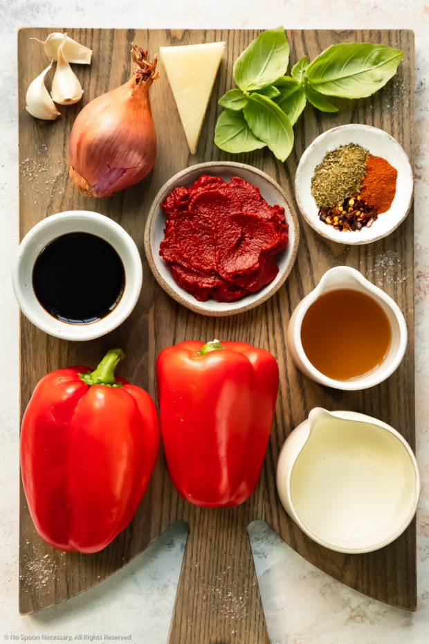 Overhead photo of all the ingredients needed to make red pepper pasta sauce neatly organized by individual ingredient on a wood board.