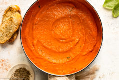 Overhead photo of Roasted Red Pepper Pasta Sauce in a large white saucepan with fresh basil leaves and cracked black pepper next to the pan.