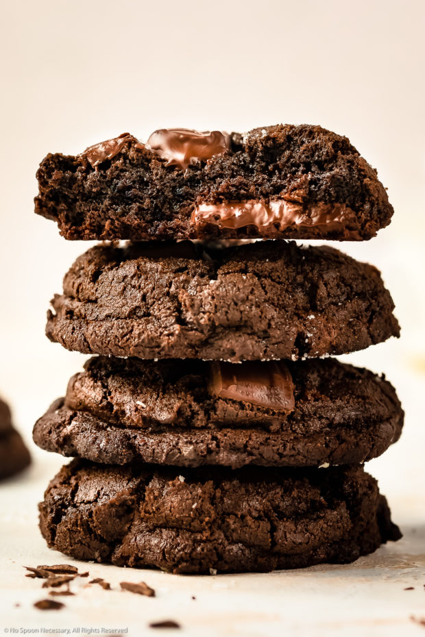 Straight on photo of a stack of triple chocolate cookies, with the focus on the top cookies fudgy center.