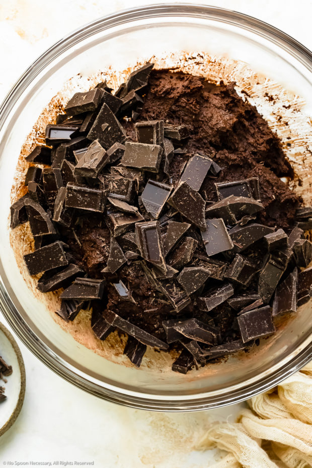 Overhead photo of raw chocolate cookie dough topped with chunks of semisweet and bittersweet chocolate in a glass bowl