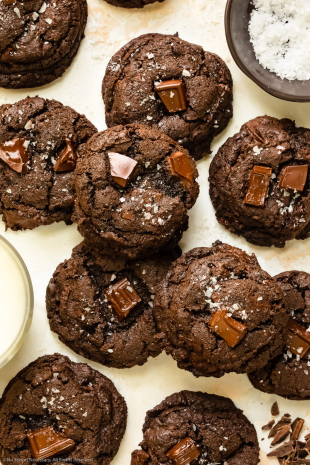 Overhead photo of chewy chocolate chunk cookies haphazardly arranged on a white wood surface.