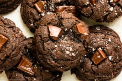 Overhead photo of a chewy triple chocolate cookie stacked on top of more cookies.
