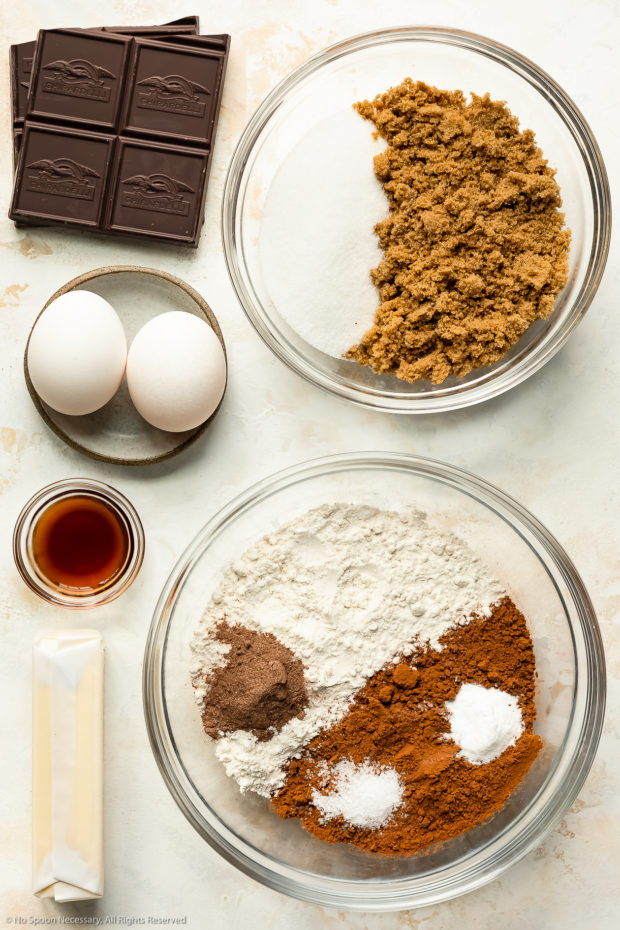 Overhead photo of all the ingredients needed to make chewy chocolate cookies neatly organized in individual glass bowls.