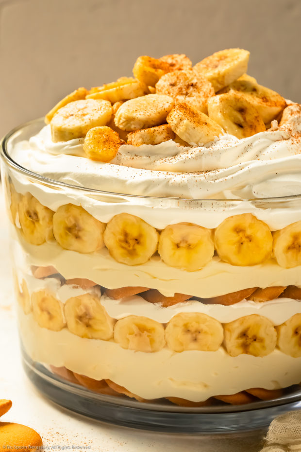 Slightly angled photo layered banana dessert with wafers, pudding, fresh bananas and Cool Whip in a large trifle dish.