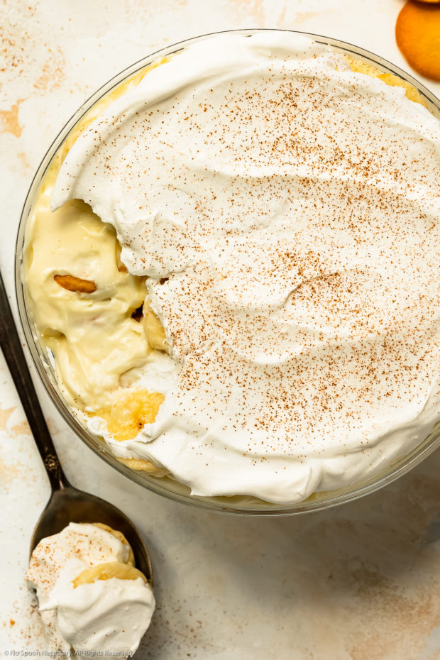 Overhead photo of no bake banana pudding in a large glass serving bowl with a spoonful of the pudding taken out of the dessert to showcase the layers.