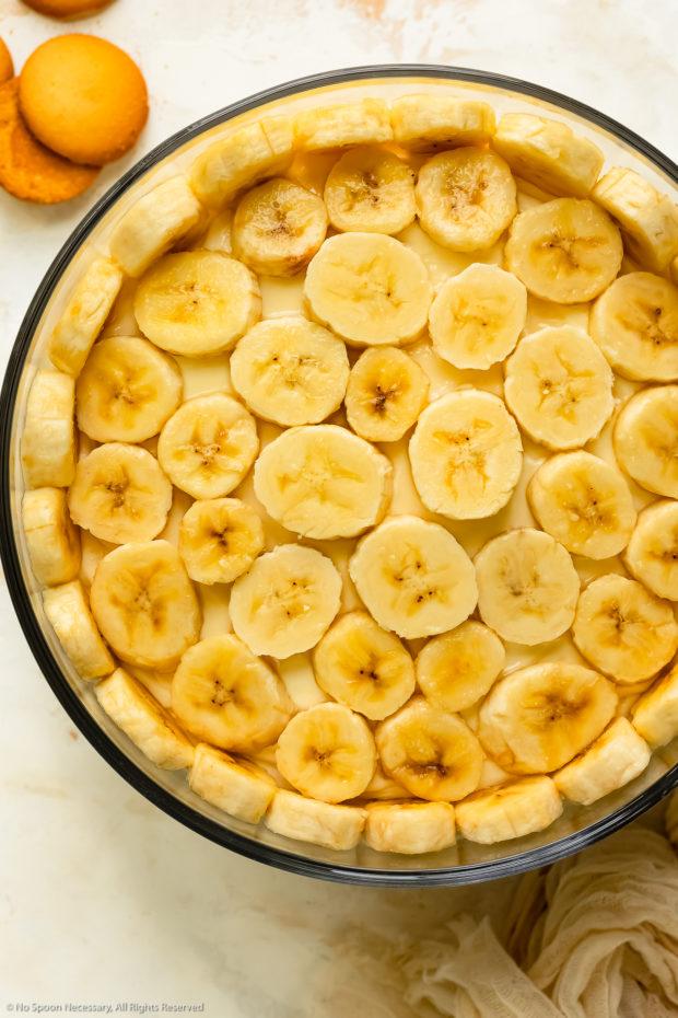 Overhead photo of fresh slices of bananas layered on pudding dessert.