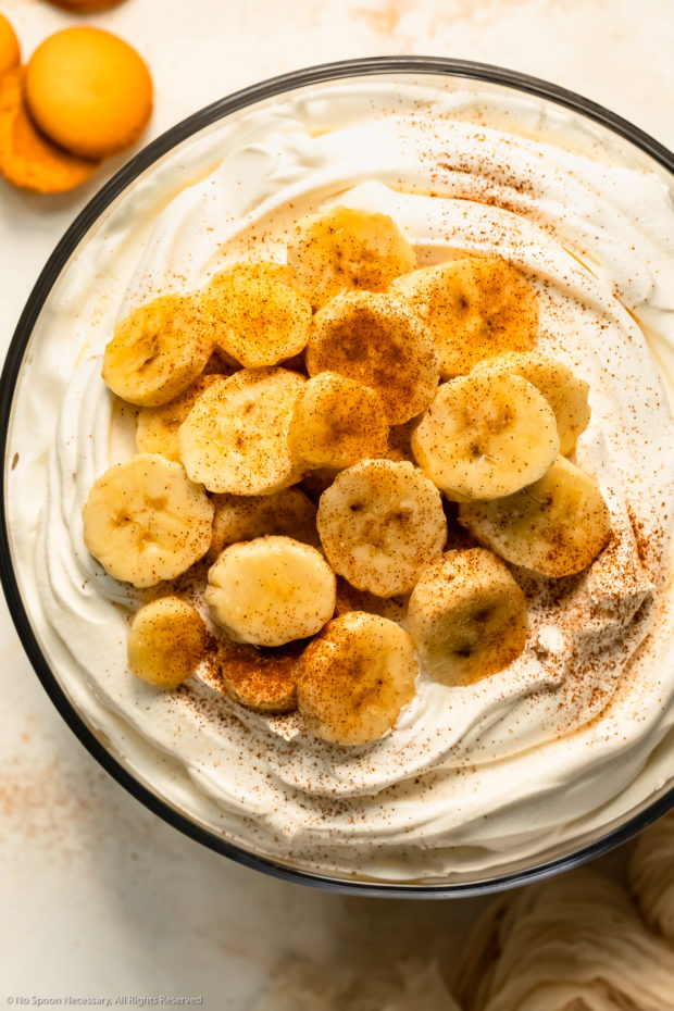 Overhead photo of fresh slices of bananas sprinkled with ground cinnamon on top of Cool Whip - photo of the top of a banana trifle.