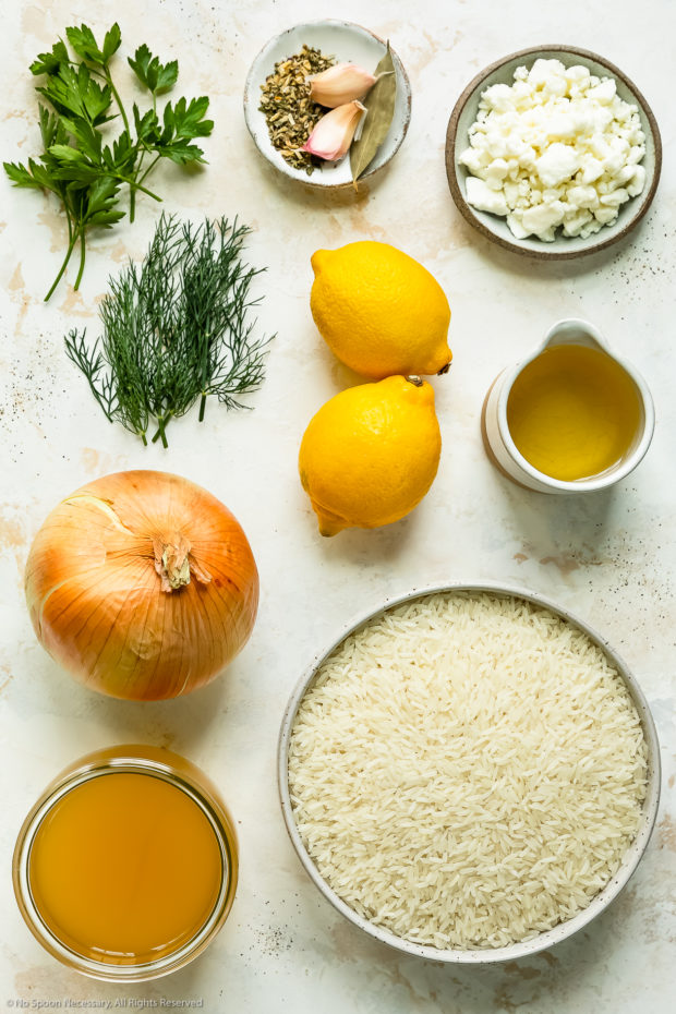 Overhead photo of all the ingredients needed to make lemon rice neatly arranged by individual ingredient on a white counter.