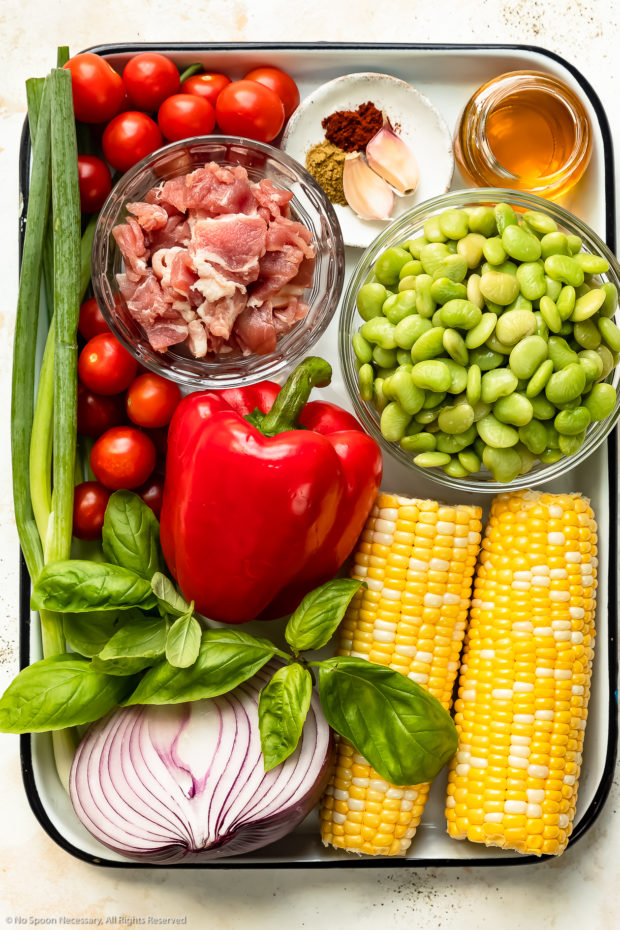 Overhead photo of all the ingredients needed to make succotash neatly arranged on a white tray.