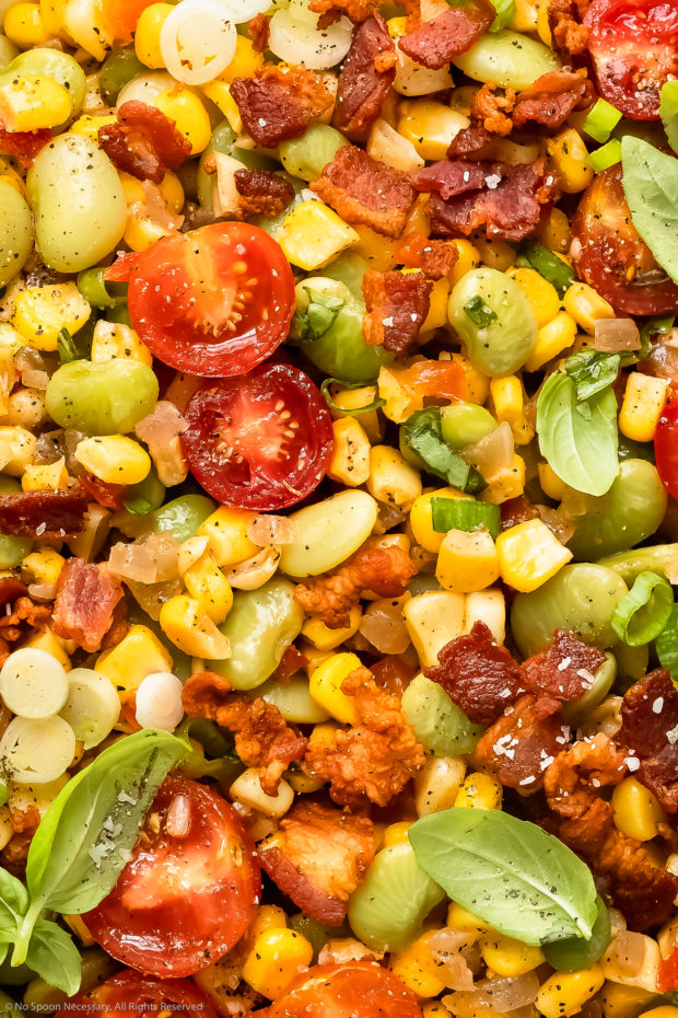 Overhead, close-up photo of succotash with corn, lima beans, tomatoes, bacon and fresh herbs.