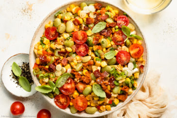Overhead photo of sweet corn succotash with bacon and tomatoes in a white serving bowl.