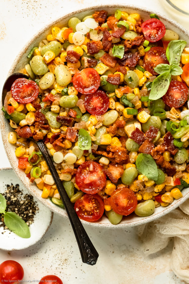 Overhead photo of succotash with bacon in a white serving bowl with a spoon inserted into the dish.