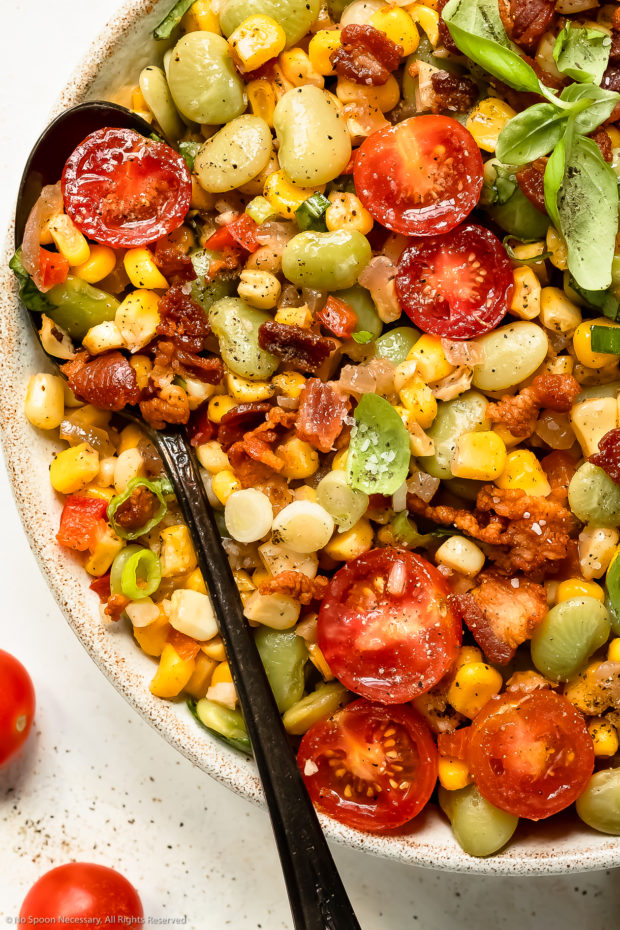 Overhead photo of lima bean and corn salad with bacon and tomatoes in a white bowl with a spoon inserted into the dish.