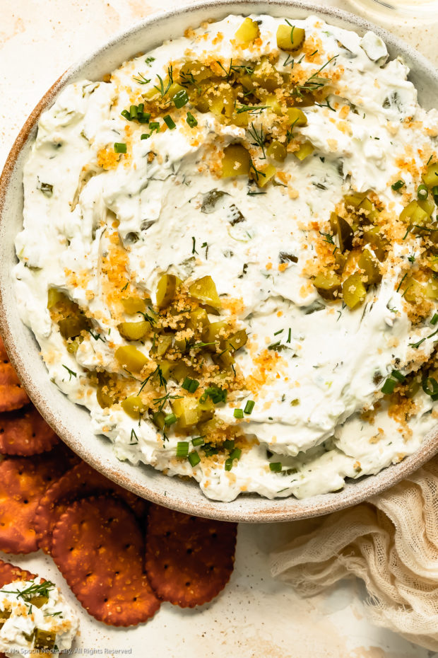 Overhead photo of copycat Ranch Pickle Dip garnished with chopped pickles, dill and crunchy breadcrumbs in a white bowl with pretzel chips next to the bowl.