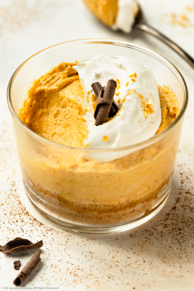 Short dessert glass containing pumpkin mousse with a bite of mousse missing from the dessert.
