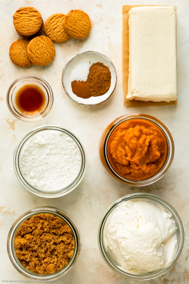 Overhead photo of all the ingredients to make pumpkin cheesecake mousse neatly organized into individual ingredients on a white surface.