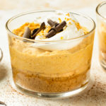 Angled, landscape photo of pumpkin mousse topped with whipped cream, chocolate curls and gold flakes in a short dessert glass.