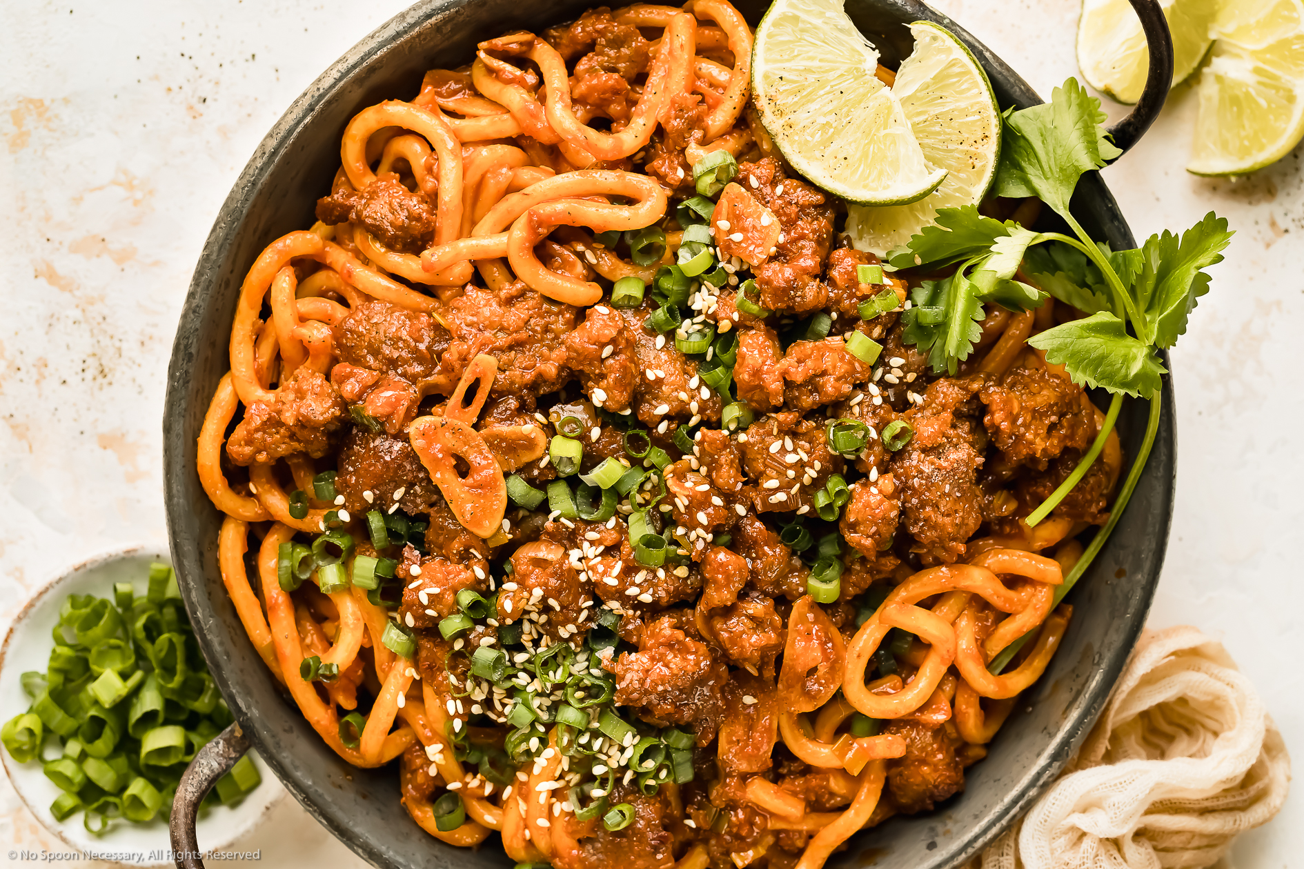 Overhead photo of Stir Fry Udon Noodles with Pork in a small wok with lime wedges and sliced scallions next to the pan.